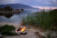 Small campfire on the shore of Lake Stock Images