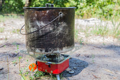 Small camping gas stove and  large smoky pot. Small camping gas stove and  large blackened pot closeup on nature Royalty Free Stock Photos