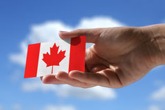 Small canadian flag. Against beautiful sky with cumulus clouds Stock Photos