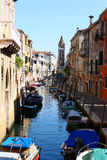 Small canal with boats in Venice. This small water canal from Venice has many boats, a bridge, a tower and some veritable Venetian old buildings Stock Photography