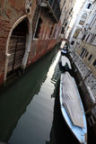 Small canal and gondola among the houses in venice Stock Image