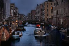 small canal with little boat with people with red umbrella and old houses in row on dusk in rainy day in Venice, Italy royalty free stock image
