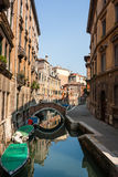 A small canal with traditional boats in Venice. Reflections of buildings and a bridge on a small narrow side canal in the city of Venice royalty free stock image