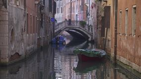 Small canal in Venice and people crossing a bridge stock footage