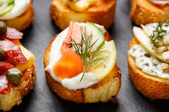 Small canape with grilled baguette with the addition creamy cheese, smoked salmon, cucumber, lemon and dill on black background Stock Images