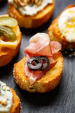 Small canape with grilled baguette with the addition ham and olives on black background Royalty Free Stock Images