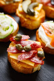 Small canape with grilled baguette with the addition of sausage, capers on  stone black background Stock Photos
