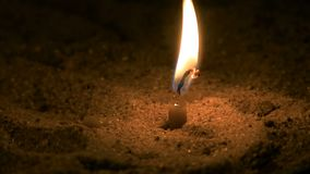 Small candle burns. It is in the sand. stock video