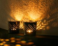 Small candle cups reflecting light. Small Christmas candle cups reflecting light and shadows on fireplace shelf stock photo