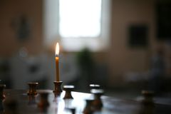 Small candle light. Small candle glowing alone,light shining through the window Royalty Free Stock Image