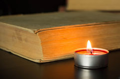 Small candle near the old book Stock Photography
