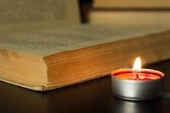 Small candle near the open book Stock Photos