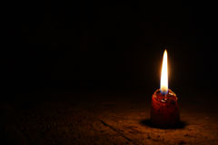 A small candle in a very dark room on the old boards Royalty Free Stock Photo