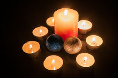 Small candles around a bigger candle and two Christmas globes Royalty Free Stock Image