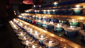 Small candles in church. Rows of burning candles in a dim church. Small firing candles in catholic church on dark stock footage
