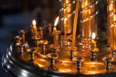 Small candles are lit in Orthodox Church. Small candles are lit in a dark Orthodox Church Stock Image