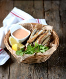 Small capelin fish baked in an oven without butter with sauce and lemon. Food Stock Photos
