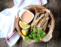 Small capelin fish baked in an oven without butter with sauce and lemon. Food Royalty Free Stock Photo