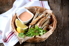 Small capelin fish baked in an oven without butter with sauce and lemon. Food Royalty Free Stock Image