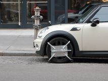 Small Car with Wheel Block Parked at Fire Hydrant Royalty Free Stock Photography