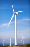Small car on a wind turbines farm Stock Photos