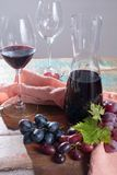 Small carafe with dry red wine, two wine glasses and grapes. On the table Royalty Free Stock Image