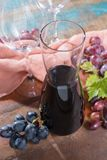 Small carafe with dry red wine, two wine glasses and grapes. On the table Stock Photos