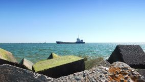 Small cargo ship entering port and sailing near breakwater stones stock video footage