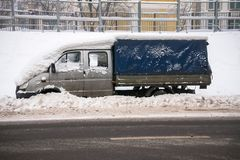 A small cargo tent van, covered with thick layer of snow and mud, on the roadway. Negative impact of heavy snowfall on the road situation. The car, covered with royalty free stock photography