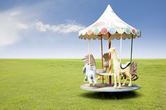 Small carousel on grass field Royalty Free Stock Images