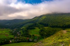 Small Carpathian village in mountains. Beautiful landscape with forested hills and agricultural fields on a cloudy morning Stock Photography