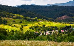 Small Carpathian village in mountains. Beautiful landscape with forested hills and agricultural fields Royalty Free Stock Images