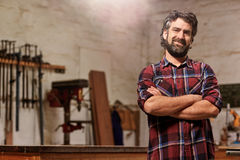 Small carpentry business owner smiling with arms crossed. Portrait of a bearded man who owns a small carpentry business, standing in his workshop with with arms stock photo