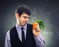 Small carrot in hand. Of a dissapointed man Royalty Free Stock Photos