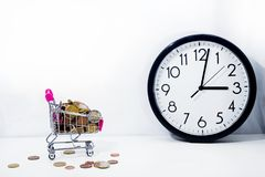 Small cart with coins on white background. Abstract composition of buying something. Small cart with coins on white background royalty free stock photography