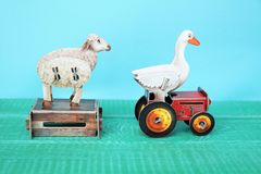 Farm animals, sheep and goose with chest and tractor. Small carton figures or childrens toys. blue background and copy space royalty free stock photos