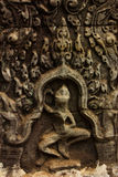 Small Carved Bas Relief in Hindu Temple with Dancing Figure. Detail of Intricately Carved Bas Relief featuring repeating vine pattern and Dancing figure in Stock Photo
