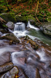 Small cascade on the river among bouders. Small cascades on the forest river among huge boulders covered with moss. dreamy Carpathian landscape Royalty Free Stock Images