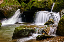 Small cascade on the river among bouders. Small cascades on the forest river among huge bouders covered with moss Royalty Free Stock Photos