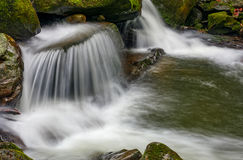 Small cascade on the river among bouders in forest. Small cascades on the forest river among huge boulders covered with moss. Fresh and clean nature environment Stock Photos