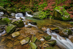 Small cascade on the river among boulders. Small cascades on the forest river among huge boulders covered with moss. dreamy Carpathian landscape Stock Images