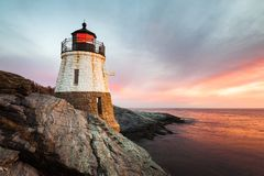 Castle Hill Lighthouse Newport Rhode Island at Sunset. Small Castle Hill Lighthouse sits on the rocky coastline of Newport, Rhode Island at sunset with the waves Stock Photography