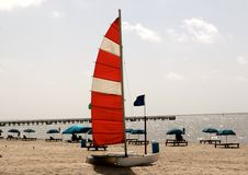A small Catamaran with a sail moored on a secluded beach Royalty Free Stock Images