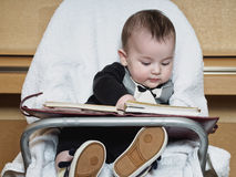 Small caucasian baby boy sitting in chear with notepad Stock Photo