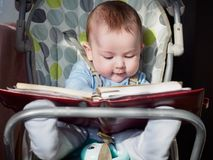 Small caucasian baby boy sitting in chear with notepad Stock Image