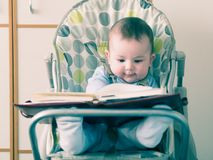 Small caucasian baby boy sitting in chear with notepad Royalty Free Stock Photos