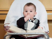 Small caucasian baby boy sitting in chear with notepad Stock Photos