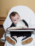 Small caucasian baby boy sitting in chear with notepad Stock Photography