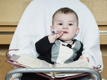 Small caucasian baby boy sitting in chear with notepad Royalty Free Stock Photo