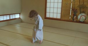 Small boy twists, twirls and dances while wearing traditional yukata. Small caucasian boy with long curly hair twists, twirls, dances and jumps on a Japanese stock video footage